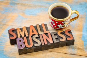 small business in wood blocks with coffee cup and brown background. type